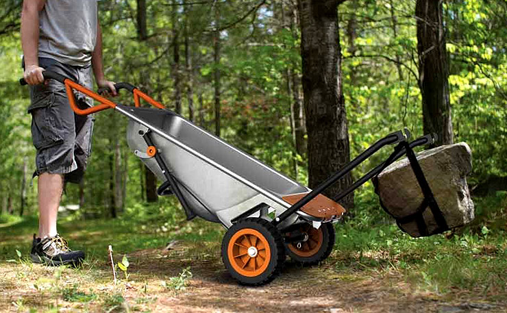 Man holding upright the WORX Aerocart wheelbarrow (WG050) in a forest.